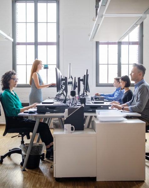 Business people at their desks in a busy, open plan office. Startup business people working at a modern office.