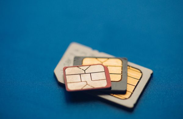 Image of Different sim cards on blue background. Broadband 5G mobile communication technology concept.