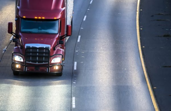 Dark red big rig bonnet American semi truck transporting commercial cargo in refrigerator semi trailer running on the turning wide multilines highway at night with turned on headlights